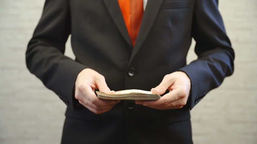 Flipping through money banknotes in slow motion 4K. Long shot of businessman with a red tie from shoulders to waist and hands holding a pack of money in focus. Shoot on an office wall background. | Shutterstock HD Video #33215842