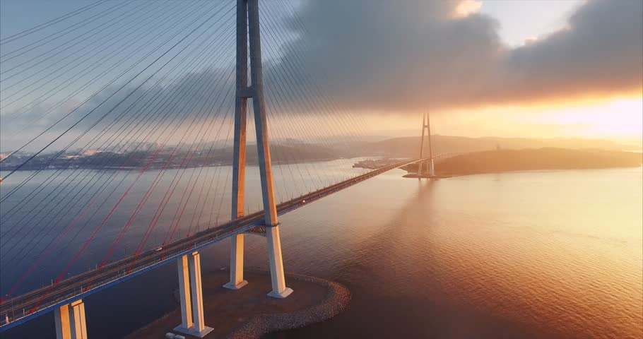 Flying backwards, aerial ascending view of cable-stayed Russian bridge across the Eastern Bosphorus strait on the way to Russian island in Vladivostok, Russia. Morning, sunrise