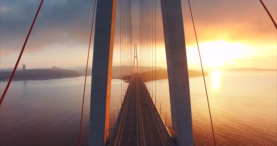 Flying above the road and between cables of cable-stayed Russian bridge across the Eastern Bosphorus strait on the way to Russian island in Vladivostok. Amazing sunrise. Aerial