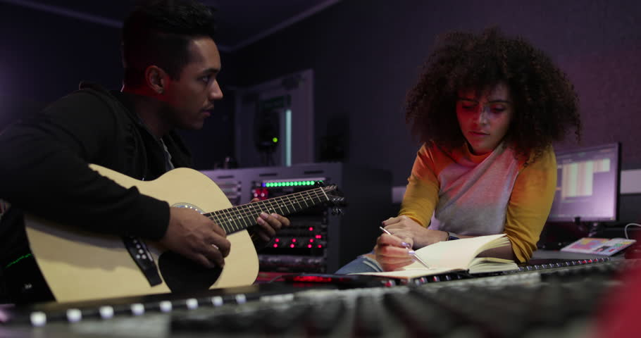 Songwriter writing lyrics in a music recording studio