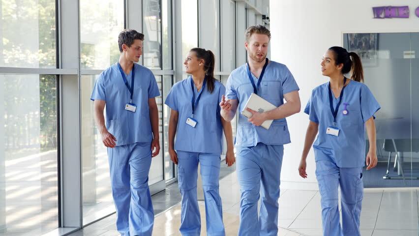 Medical Interns Wearing Scrubs Walk Towards Camera in Busy Hospital