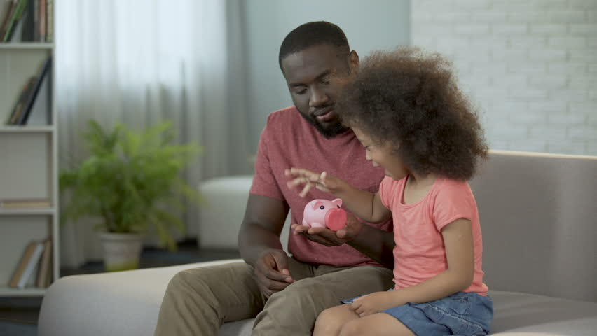 Caring father teaching child to save money, putting coins into piggy bank | Shutterstock HD Video #33287683