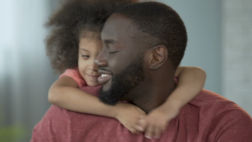 Cute girl hugging her dad around neck tightly with her little hands, tenderness
