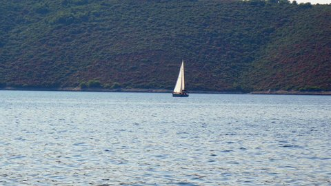 Sailing boat sailing in Adriatic sea with green forest on small island in background. Filmed from moving sailing boat in 4k.