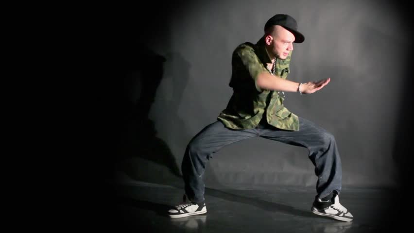 Hip-hop dancer in cap dances in photo studio with black background
