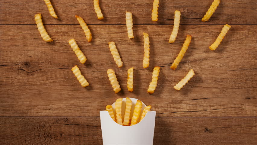 French fries falling into and pouring out of paper holder on brown wooden table - stop motion animation #33300943