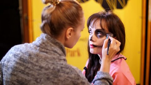 Halloween party, make-up artist draws a terrible makeup on the face of a brunette woman for a Halloween party. in the background, the scenery in the style of Halloween is seen.