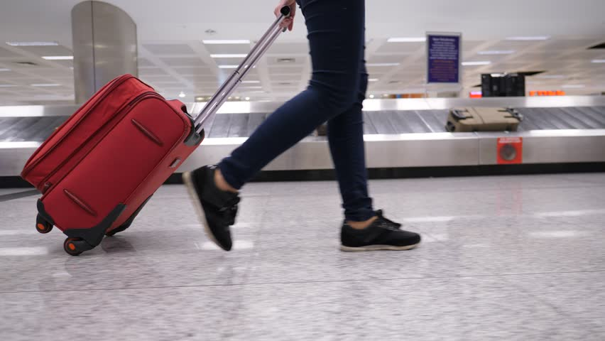 Passenger woman walk with trolley case against baggage carousel, low half view of slender female legs and medium wheeled bag, smooth tracking shot. Luggage conveyor belt number nine seen on background