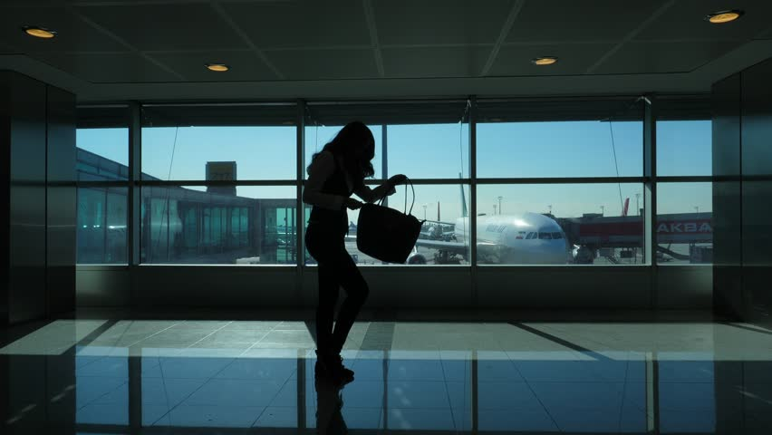 ISTANBUL - NOVEMBER 02, 2017: Female passenger (model released) close handbag, full length black silhouette against large window of terminal, parked aircraft seen outside. Woman zip up soft bag | Shutterstock HD Video #33314002