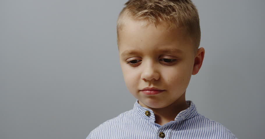close up of the sad little blonde boy wiping his eyes with a napkin after crying. Portrait. Wall background. Indoor #33316636