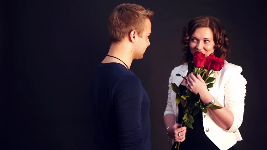 young man presents red roses wor a woman whos waiting for him