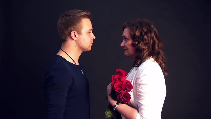 young man kissing his woman with red roses
