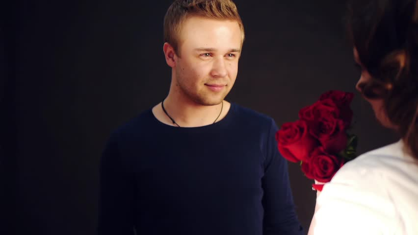 young man presenting red roses for his young woman