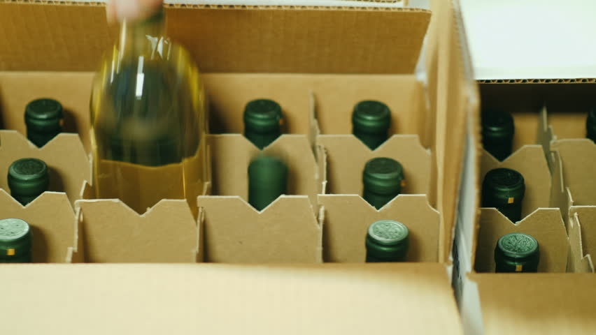 Close-up of putting bottles of wine in a box. Preparation for shipment to the retail sales network Royalty-Free Stock Footage #33337678
