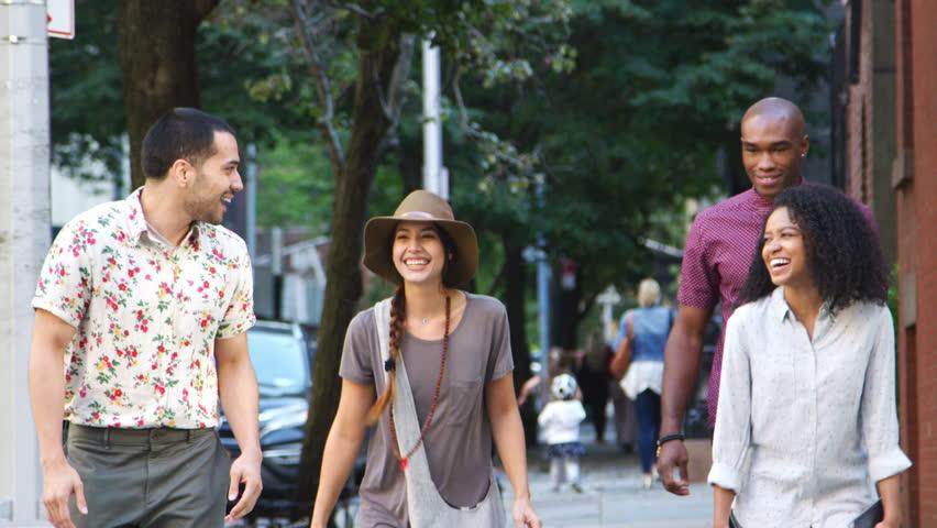 Group Of Friends Walking Along Urban Street In New York City