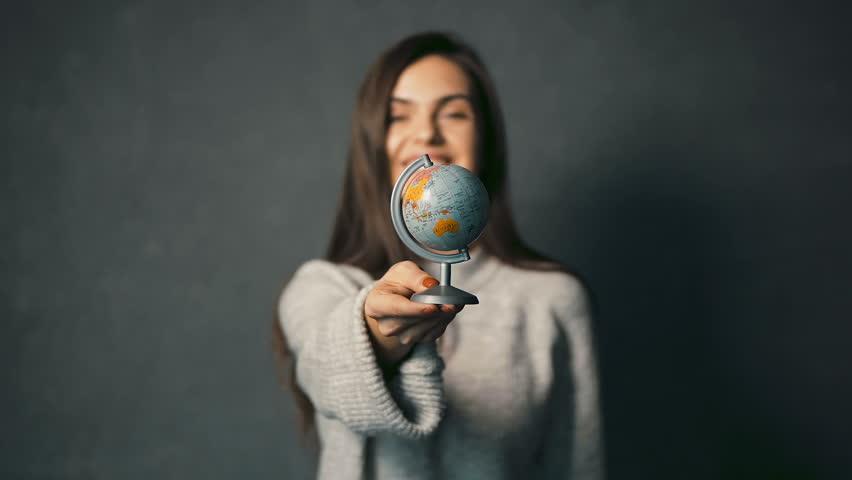 Beautiful dark-haired girl in warm grey sweater turning the globe, indoor isolated shot