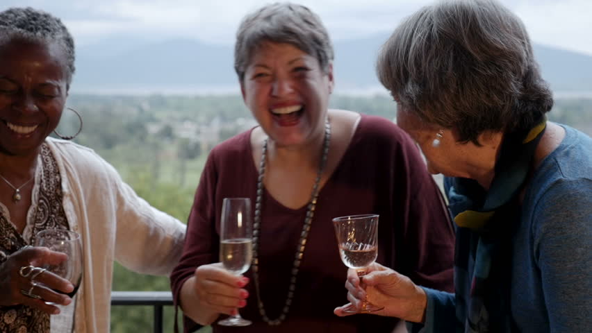 Mixed racial group of senior women friends in their 60s laughing out loud on a balcony holding wine glasses with an amazing mountain view in slow motion
