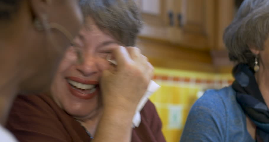 Woman wiping tears of joy with her two other friends all over 60 laughing and having a great time together at a social event