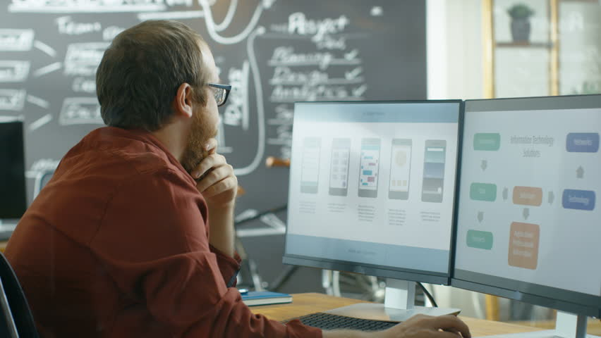 Male Mobile Video Game Application Developer Works on a Personal Computer, Designing Wireframe, He's Smooths the Beard in Thinking Gesture. Shot on RED EPIC-W 8K Helium Cinema Camera. | Shutterstock HD Video #33367219