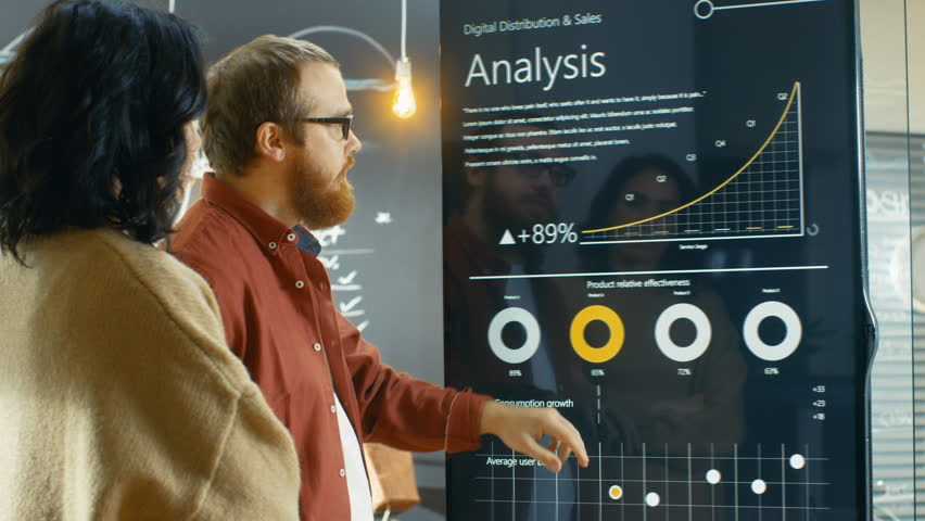 Female Developer and Male Statistician Use Interactive Whiteboard Presentation Touchscreen to Look at Charts, Graphs and Growth Statistics.  Shot on RED EPIC-W 8K Helium Cinema Camera.
