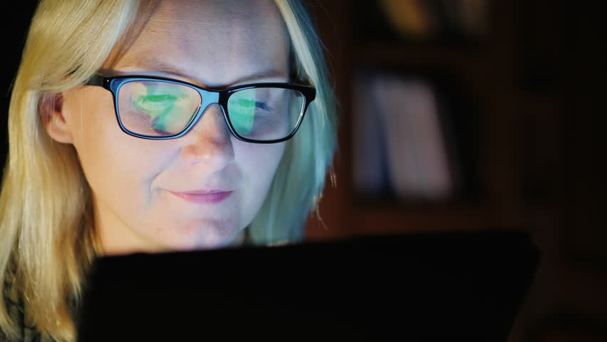 Portrait of a young woman, close-up. Works with the tablet, the screen is reflected in her glasses | Shutterstock HD Video #33376960