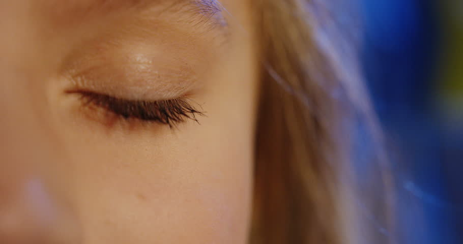 Close up of the half face of the blonde teen girl opening an eye and looking into the camera. Blue blurred background. Portrait. Indoors | Shutterstock HD Video #33377293