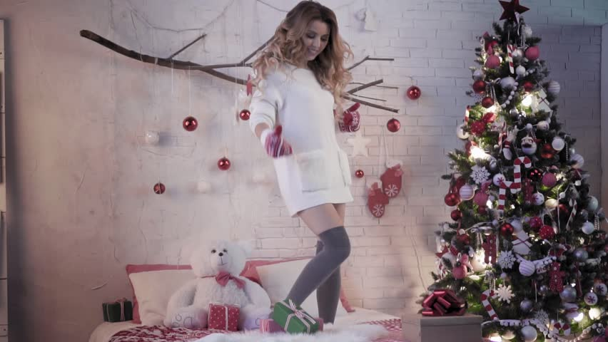 Attractive brunette dancing on a bed in red mittens near a Christmas tree