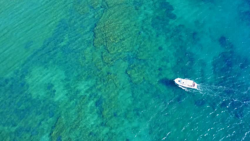 Aerial view video taken by drone of boat cruising in Caribbean tropical beach with turquoise - sapphire waters