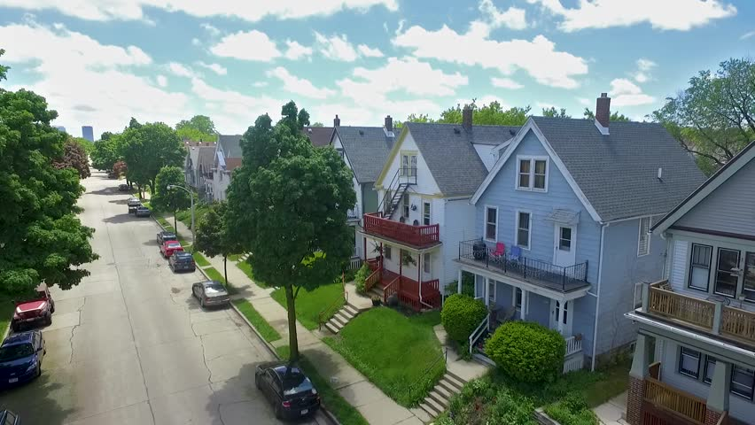 An aerial drone shot of a Milwaukee neighborhood showing streets, cars, trees, houses, blue sky, clouds and the city in the background on a bright and sunny day.