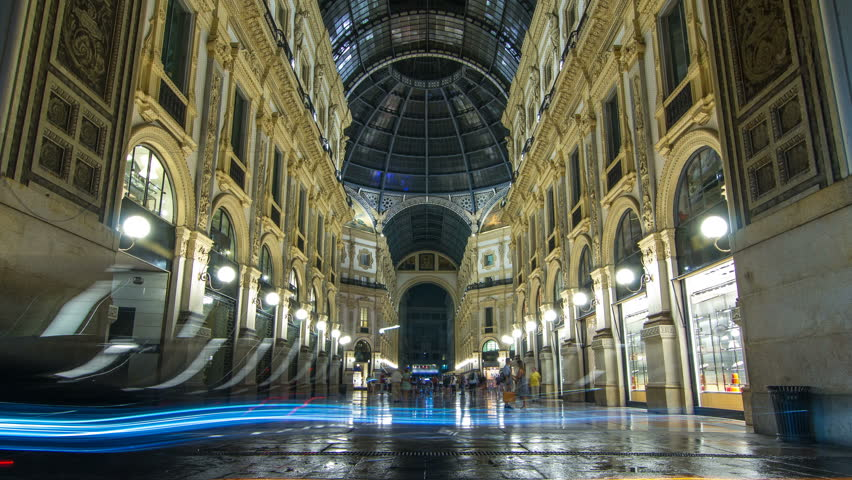 Entrance to the Galleria Vittorio Emanuele II timelapse from Via Tommaso Grossi at night. This gallery is tourist attraction of Milan. People walking inside