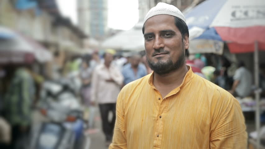 A mid shot of a confident smiling Muslim young man standing and looking into a camera in a busy market