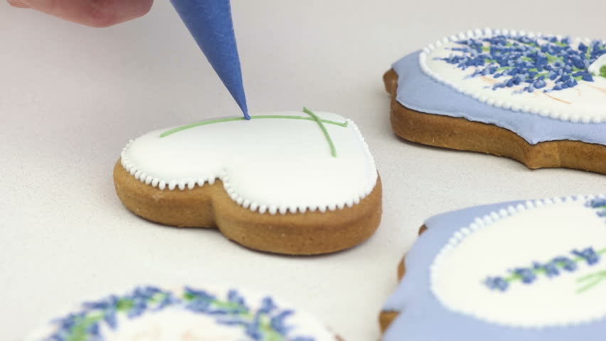 Confectioner decorates gingerbread or freshly baked cookies | Shutterstock HD Video #33400165