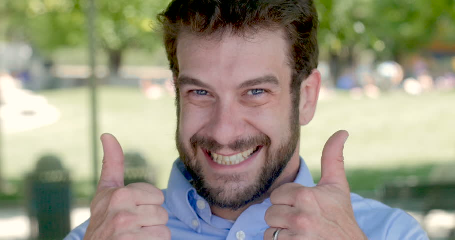 Happy handsome millennial man in 30s giving two thumbs up and smiling outdoors