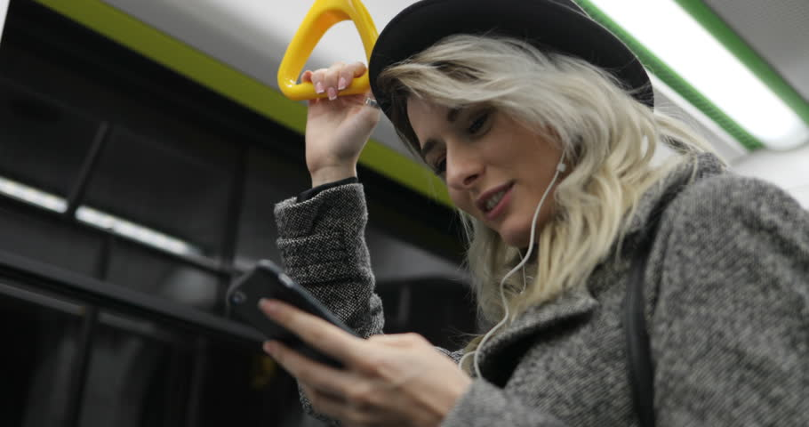 Portrait of cute girl in headphones holds the handrail, listening to music and browsing on mobile phone in public transport. City lights background