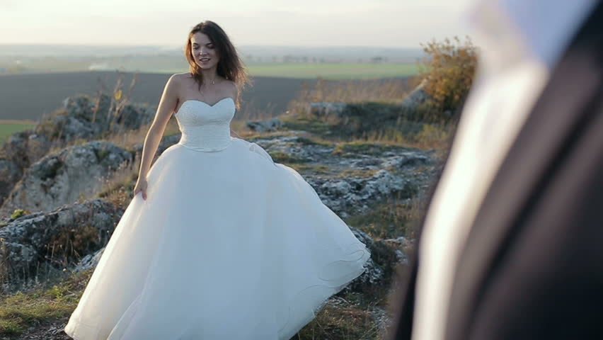 The bride spins near the groom on the mountains rock at the sunset. Slow motion | Shutterstock HD Video #33430705