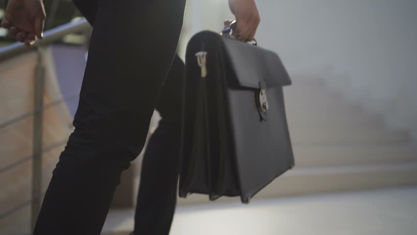 Slow motion: Unrecognizable businessman or lawyer in formal suit with briefcase goes upstairs in centrelink offices of company or in the building of state authority. | Shutterstock HD Video #33441757