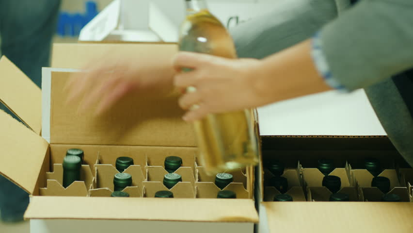 Packing of finished products in the winery. Bottles with white wine are put in cardboard boxes Royalty-Free Stock Footage #33442117