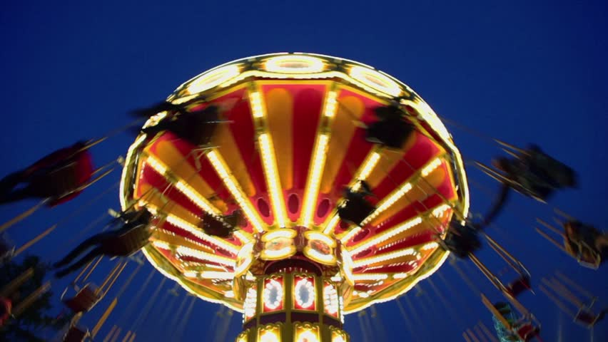 People fly on chairs during ride on round circling carousel with illumination Royalty-Free Stock Footage #3345392