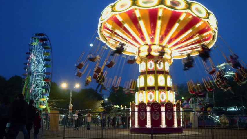 People fly on chairs during ride on round circling carousel and Ferris wheel with illumination at park Royalty-Free Stock Footage #3345437
