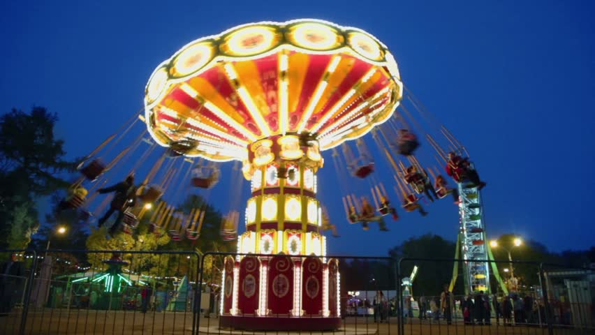 People fly on chairs during ride on round spins carousel and Ferris wheel with illumination at park Royalty-Free Stock Footage #3345452