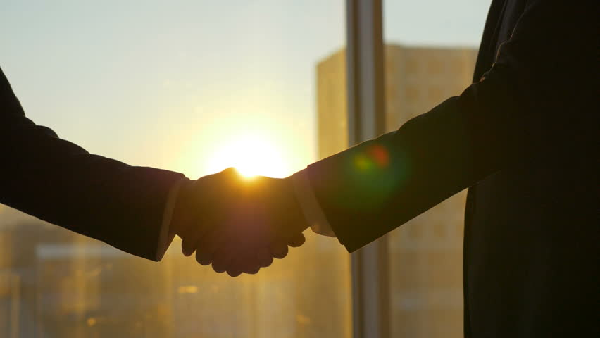 The two men handshake on the sunset background. slow motion