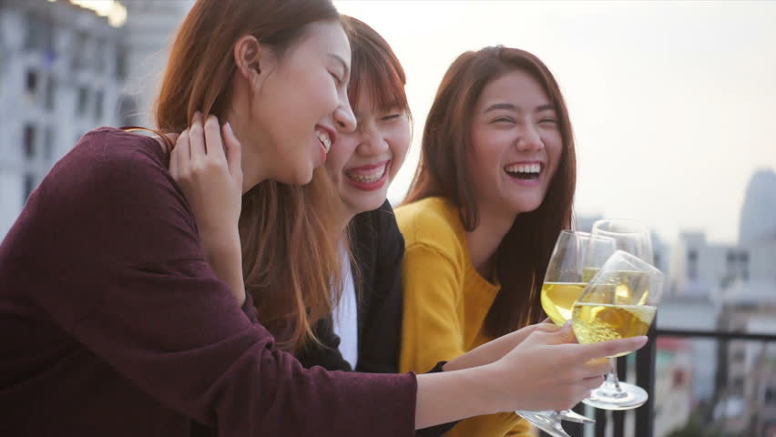 Outdoor shot group of happy teen people having fun toasting drinks sit together on rooftop terrasse at sunset. Young asian lady friends hanging out, Holiday celebration festive party. 4k resolution. | Shutterstock HD Video #33484546