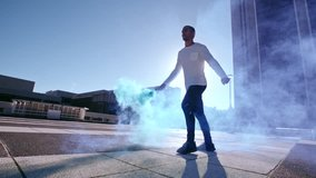 Urban man with smoke grenade jumping high and performing a flip. Fit male practicing parkour in urban space with smoke stick.