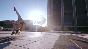Young man and woman practicing parkour in the city. Urban runners in action doing flips outdoors.
