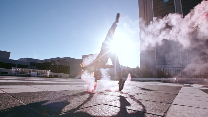 Young woman with colorful smoke grenade jumping high performing a flip outdoors in city. Female with smoke sticks practicing tricking over urban city space.