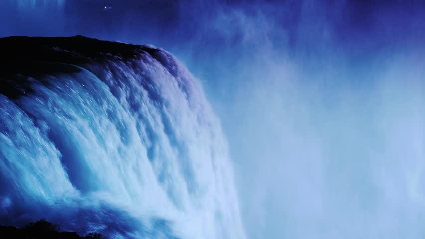 Night illumination at Niagara Falls. The stream of water is illuminated by floodlights from the Canadian coast