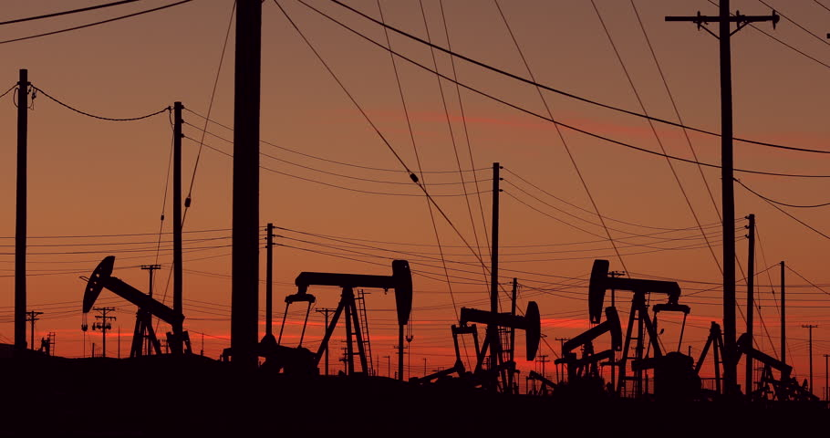Silhouette at sunset of a nodding donkey pumping fossil fuel crude up from the ground on an oil field