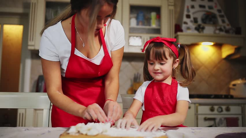 Happy family in the kitchen mom and daughter in the kitchen playing with flour to have fun and mold the patties in the kitchen in the same red aprons. stedicam #33496234