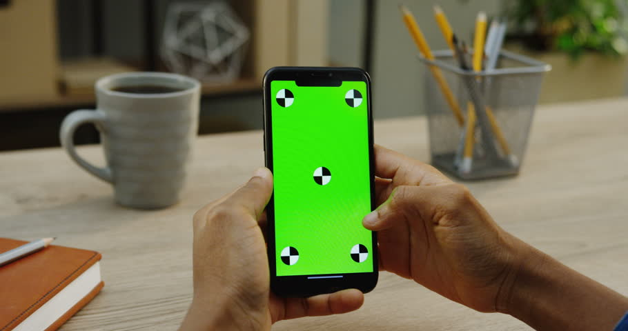 Black smart phone in caucasian male hands being held vertically. Fingers scrolling on it. Green screen. Chroma key. Tracking motion. Wooden office desk with cup of tea background. Close up