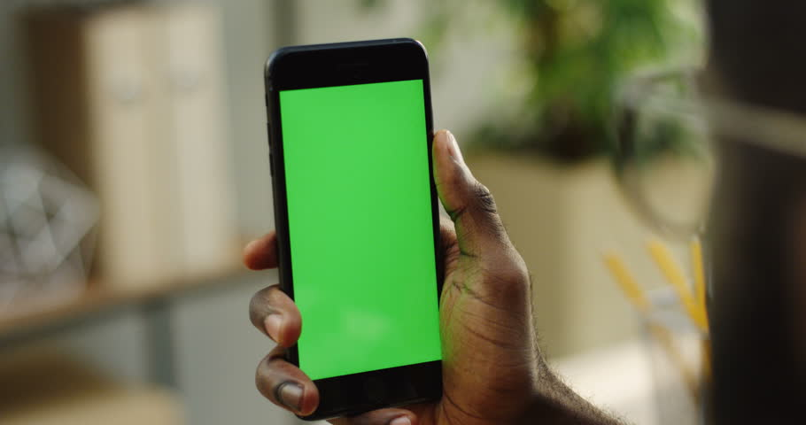 African American male hands holding a blacksmart phone vertically and scrolling on it. Green screen. Chroma key. Blurred room on the background. Close up | Shutterstock HD Video #33502942